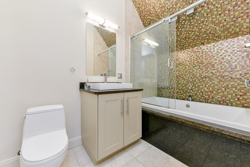 A bathroom with a shower next to a sink next to a toilet.