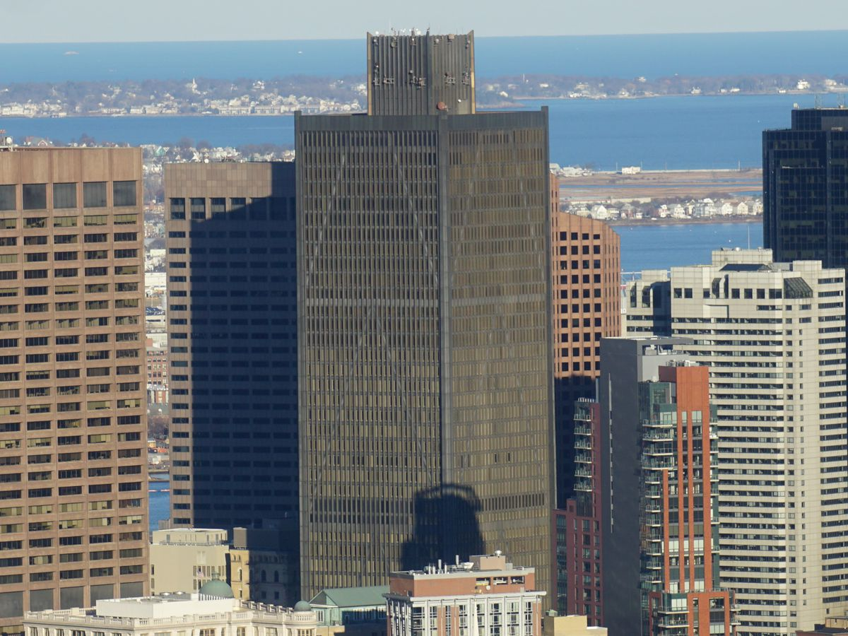 A group of tall city buildings in Boston. In the center of the group of buildings is One Boston Place which has a dark grey facade with many windows.