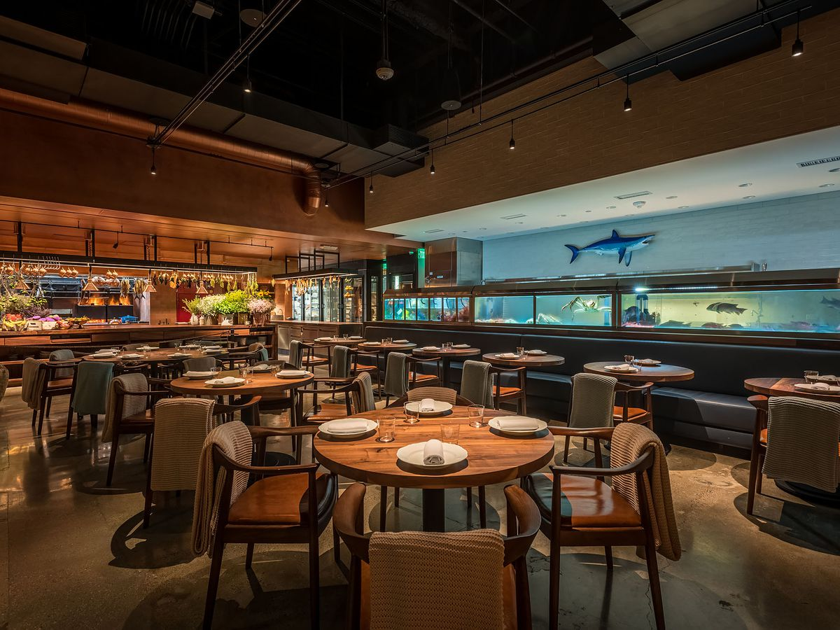 Dining room, dimly lit, with fish tanks and decor, at Angler, Los Angeles .