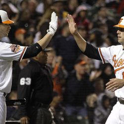 Baltimore Orioles' Nolan Reimold, left, high-fives Mark Reynolds after Reynolds scored on a single by Robert Andino in the second inning of a baseball game against the New York Yankees in Baltimore, Wednesday, April 11, 2012.