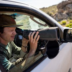 Hawkwatch International research associate Dustin Maloney uses a scope to look for activity in a golden eagle nest on Antelope Island on Wednesday, May 19, 2021.