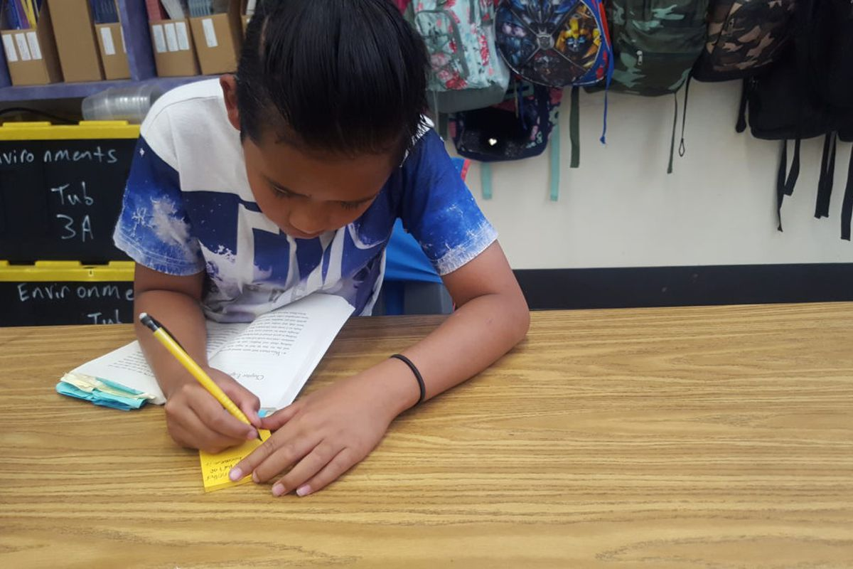 A fourth grader in Aurora's Peoria Elementary takes notes while reading.