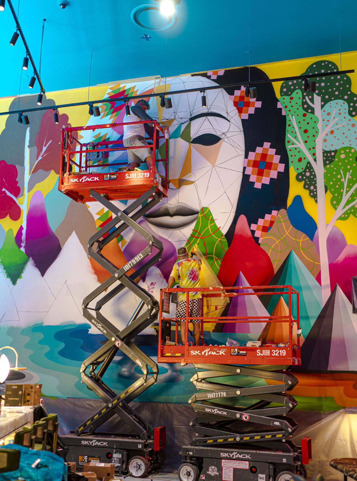 A man on a scissor lift paints a mural