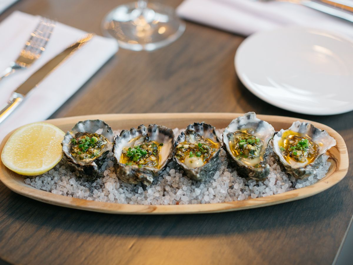 A row of oysters on the half shell on ice topped with green garnish and flanked by a half slice of lemon.