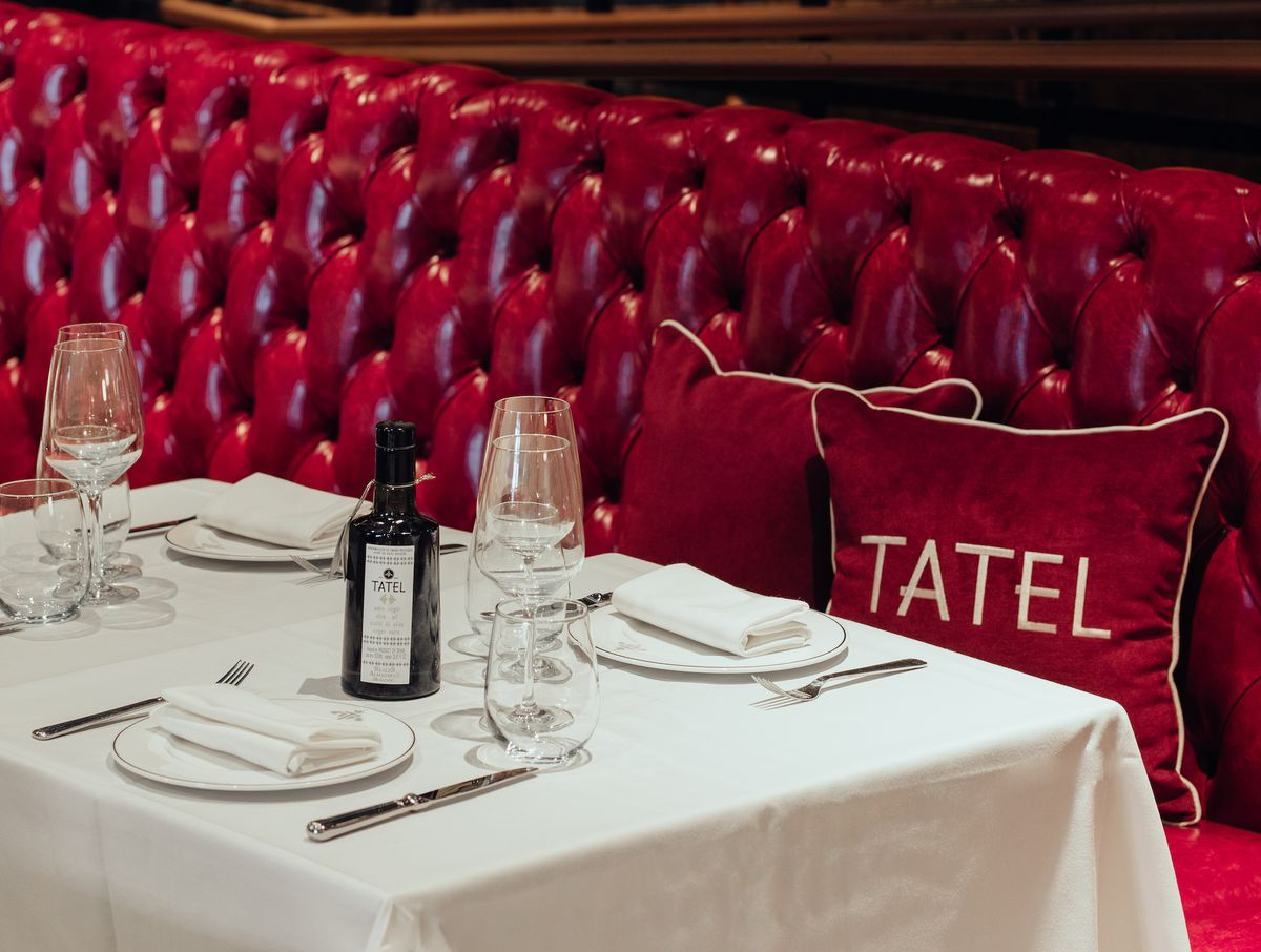 A bright red booth and white tablecloth at a fine dining restaurant.