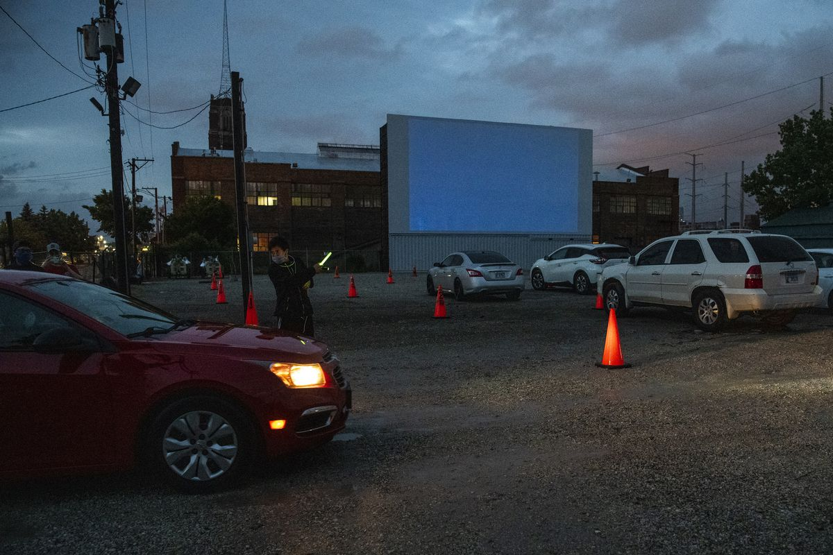 An usher guides patrons to their parking spot at ChiTown Futbol's first night of drive-in movies on Tuesday. | Tyler LaRiviere/Sun-Times