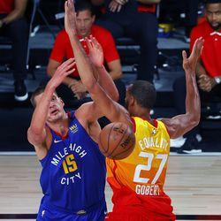 Denver Nuggets' Nikola Jokic (15) loses the ball as he drives against Utah Jazz' Rudy Gobert (27) during the first quarter of an NBA basketball game Saturday, Aug. 8, 2020, in Lake Buena Vista, Fla.