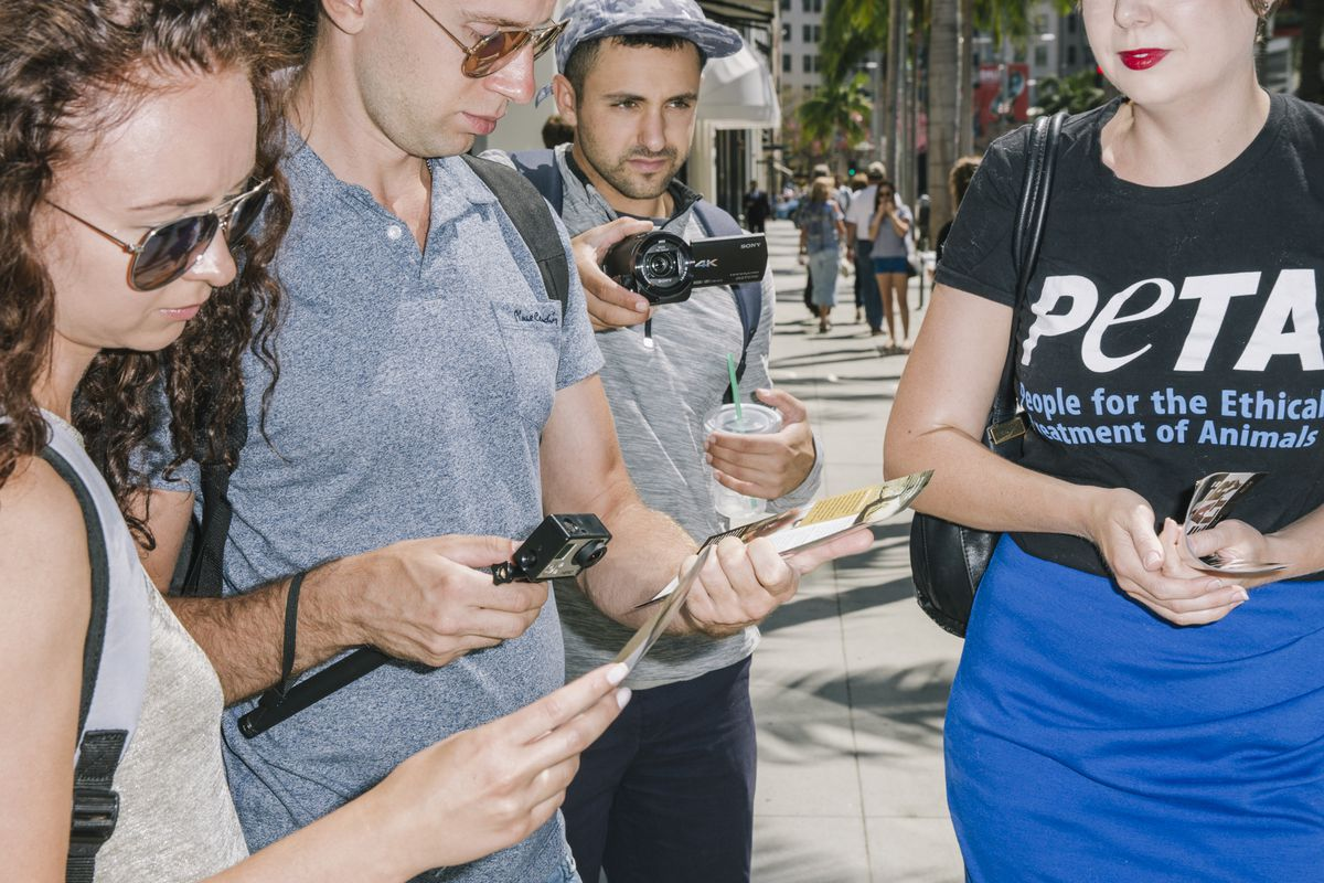 Two bystanders take PETA fliers from a woman in a PETA T-shirt as a man photographs them.