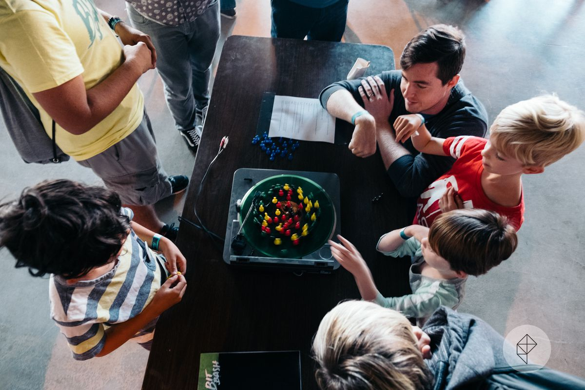 Players gather around a turntable, taking turns placing colored pawns.
