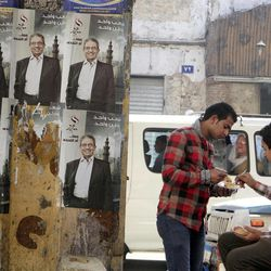 """Egyptians eat in front of posters of Presidential candidate Amr Moussa for the upcoming elections in Cairo, Egypt, Thursday, April 26, 2012. Egypt's election commission announced the final list of 13 candidates this week for next month's presidential elections. Arabic on the posters read, """"Amr Moussa, one people one nation."""""""