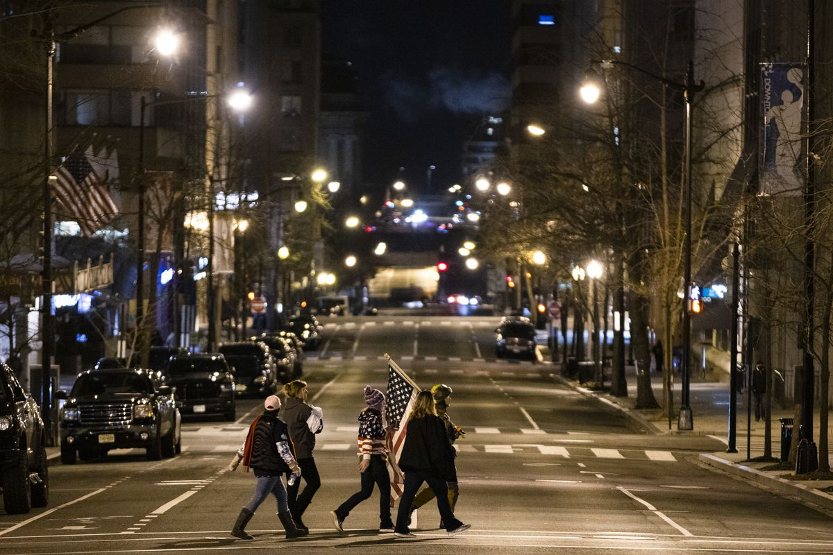 Five people walk across a street at night holding a large american flag. One woman wears an American flag sweater.