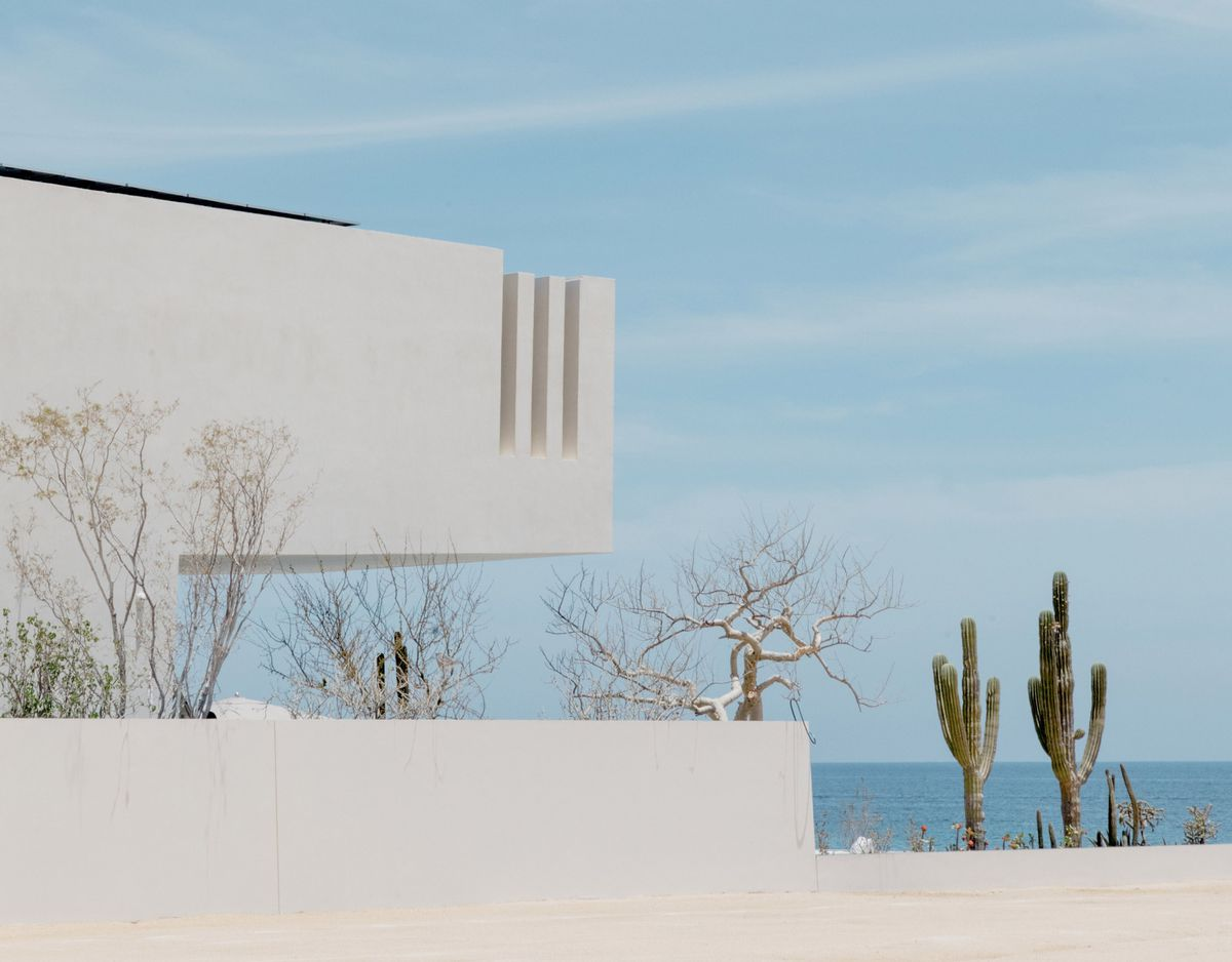 Angular white house with a cantilever faces the ocean.