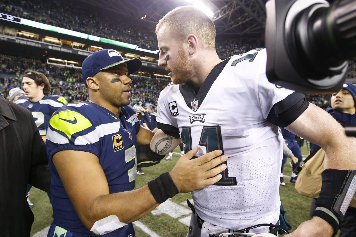Seattle Seahawks quarterback Russell Wilson greets Philadelphia Eagles quarterback Carson Wentz following a 24-10 Seattle victory at CenturyLink Field.