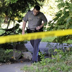 State Trooper Matt Losh emerges from the backyard of a home in New Fairfield, Conn., where a fatal shooting took place, Thursday, Sept. 27, 2012. Police say Jeffrey Giuliano shot a masked teenager in self-defense during what appeared to be an attempted burglary early Thursday morning, then discovered that he had killed his son, Tyler.