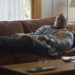 The black father in the commercial wakes up with Cheerios on his chest from his daughter's friendly gesture to eat healthy.