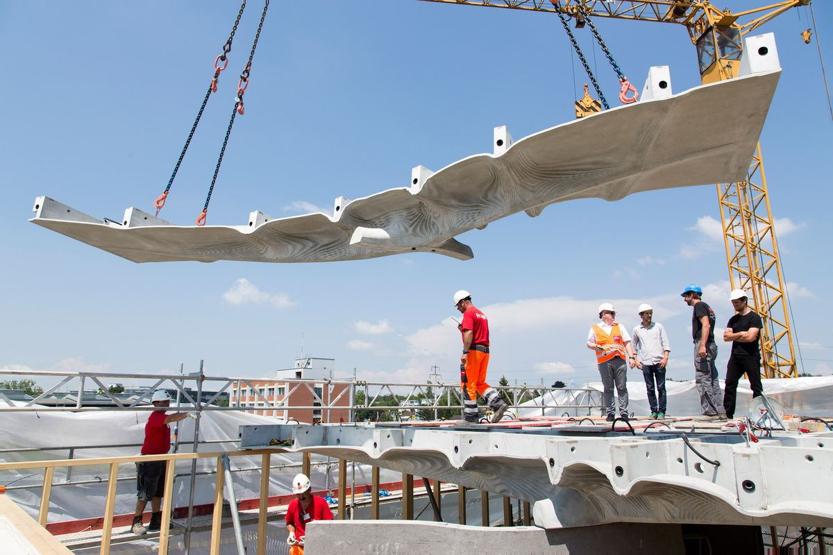 Crane lowering concrete slab into place