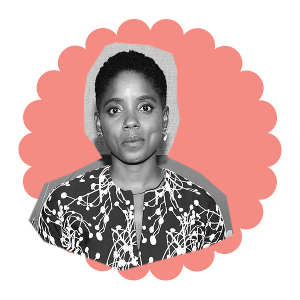 A black and white photo of Janicza Bravo with short cropped hair, wearing a black and white printed blouse.