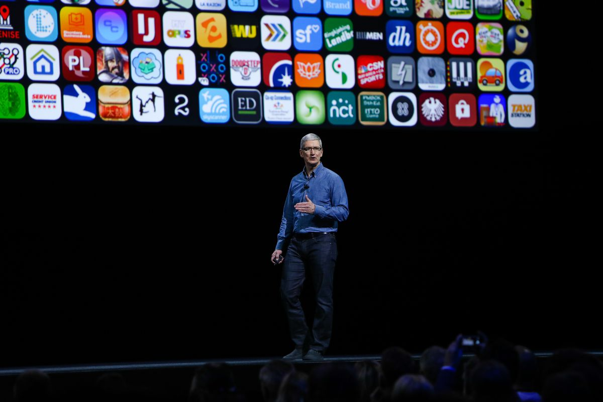 Apple CEO Tim Cook onstage with a wallpaper of app icons behind him