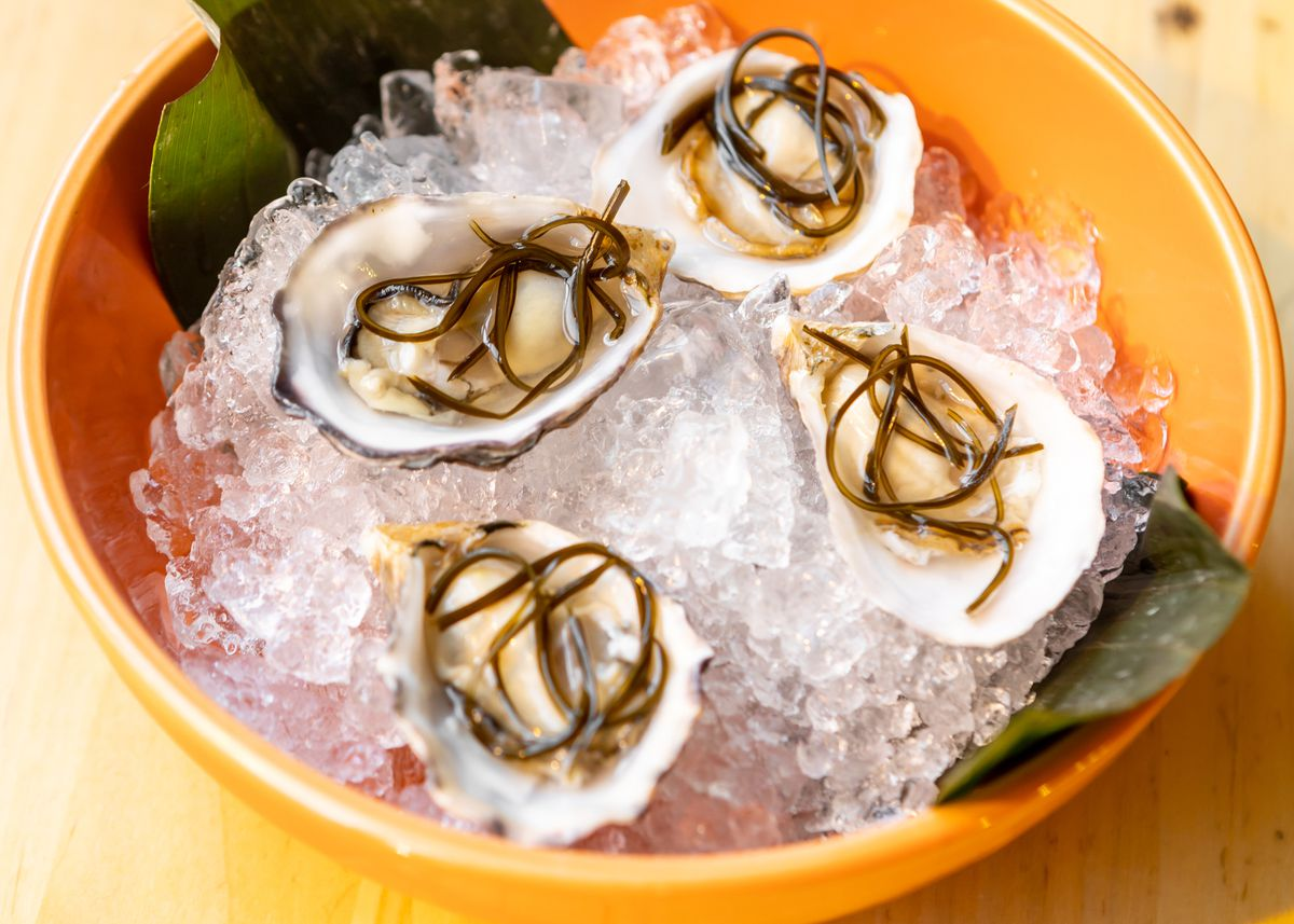 Four raw oysters on ice, topped with kombu fina'denne'