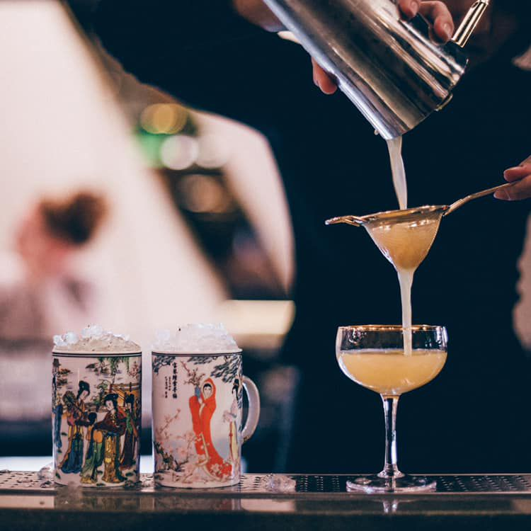 A drink is poured into a coupe through a strainer.