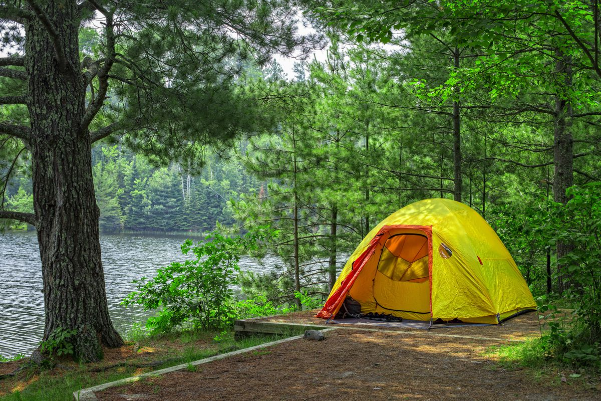 a tent perched above a lake.