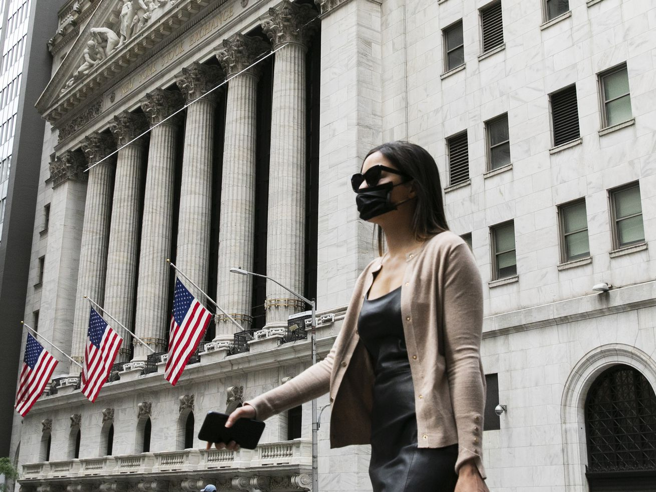 A woman wearing a mask passes the New York Stock Exchange Tuesday, during the coronavirus pandemic.