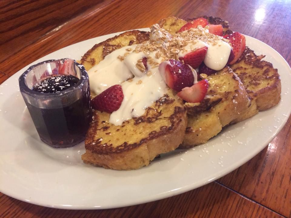 French toast covered with strawberries and cream, and a small glass ramekin of blackberry compote on the side