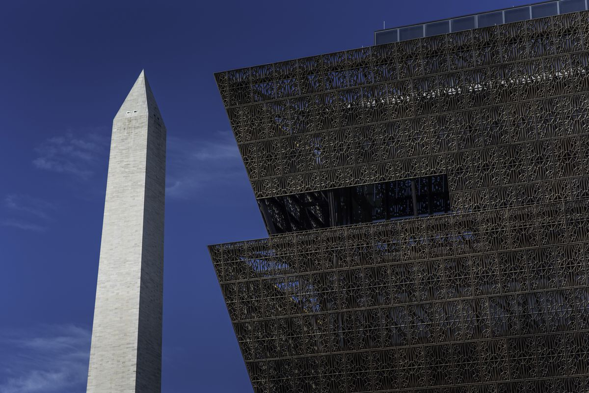 A shot showing the top two layers of a bronze clad museum with the Washington Monument, a tall obelisk, in the background.