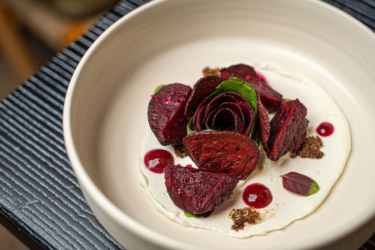 A beet salad with beet chips and pickled beets on goat cheese quark.