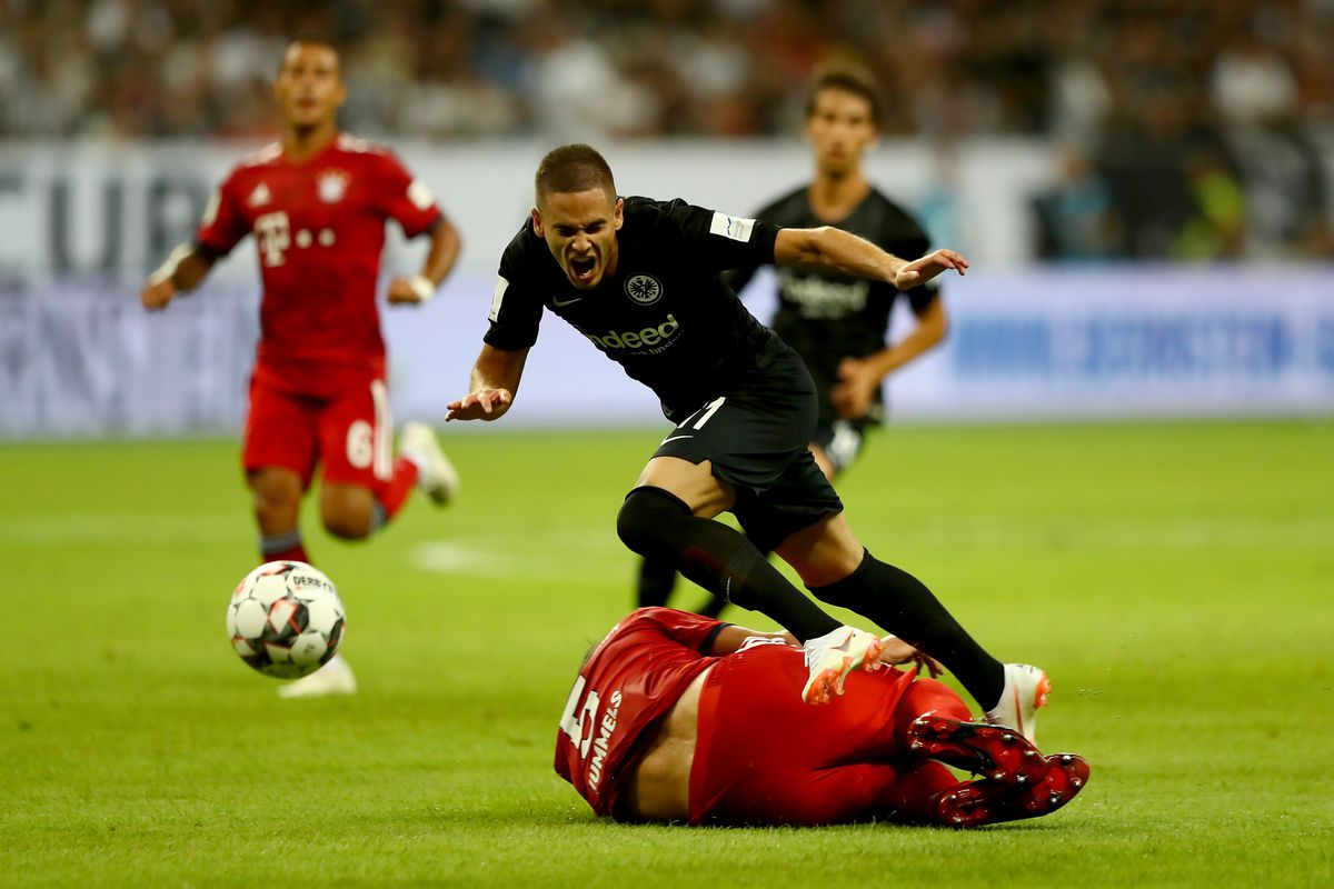 FRANKFURT AM MAIN, GERMANY - AUGUST 12: Mijat Gacinovic (L) of Frankfurt and Mats Hummels of Muenchen battle for the ball during the DFL Supercup 2018 between Eintracht Frankfurt and Bayern Muenchen at Commerzbank-Arena on August 12, 2018 in Frankfurt am Main, Germany.