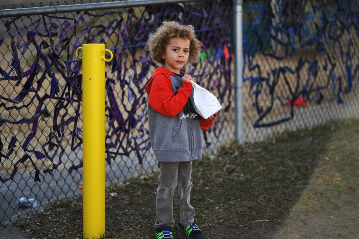 Child holds a sack lunch at a Denver grab-and-go meal site.