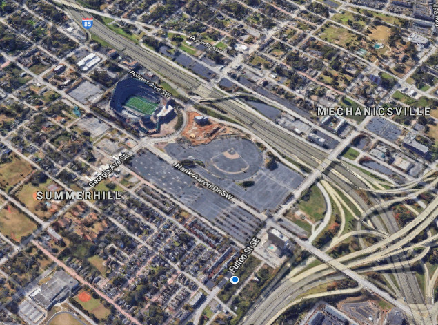 An aerial image of highways and a baseball stadium with many parking lots.
