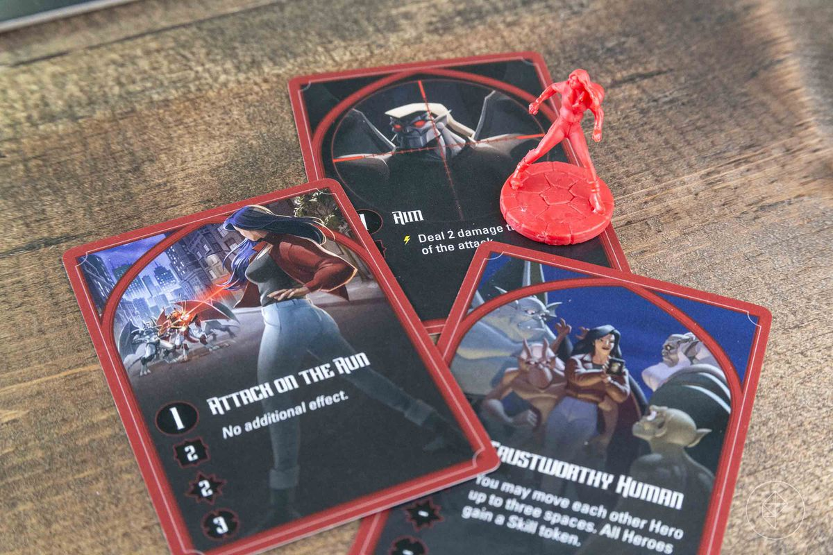 A red character with a collection of her cards, showing her taking aim and shooting a gun.