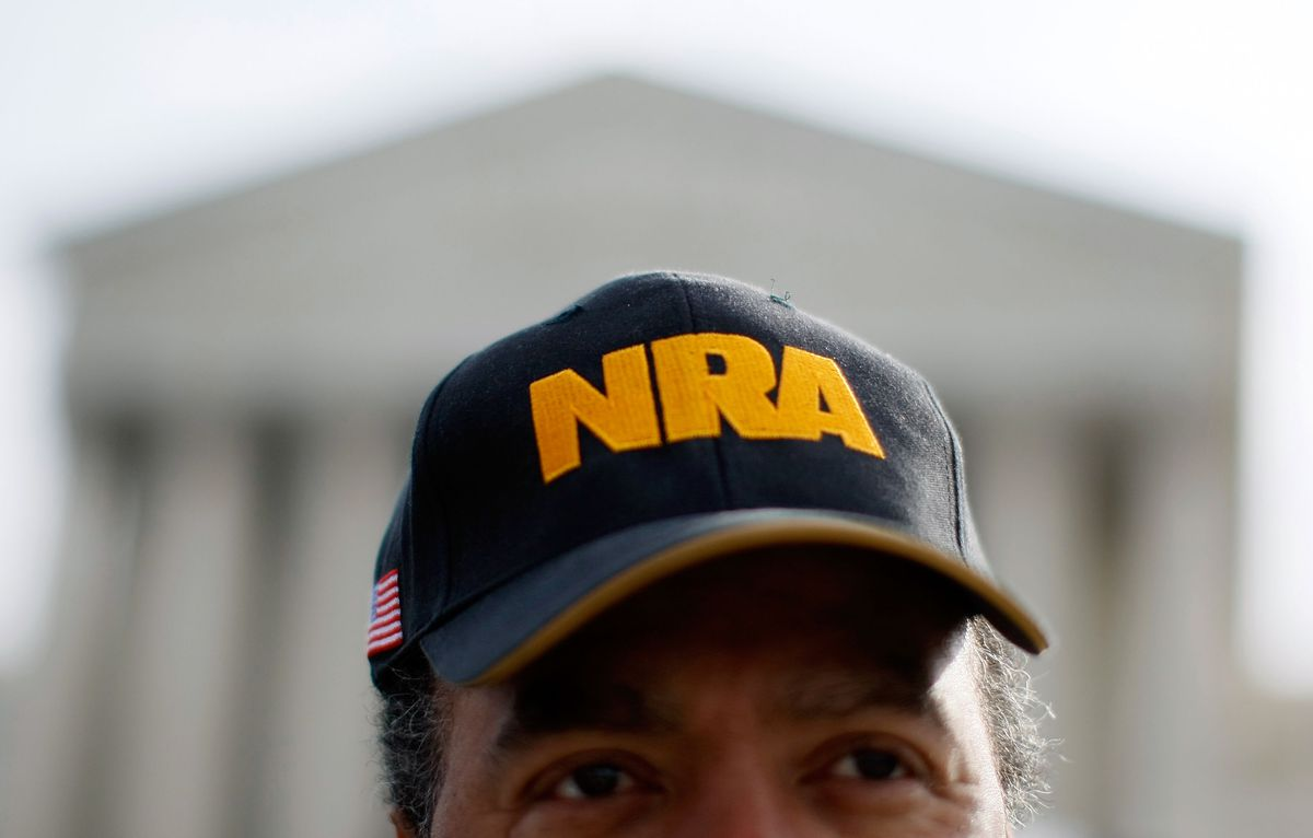 A man wears an NRA hat while showing his support for gun rights in front of the US Supreme Court.