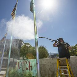 Chad Rasmussen, owner of Royce Industries, uses a pressure washer to clean paint from the flagpoles at the Salt Lake County District Attorney's Office building in Salt Lake City on Friday, July 10, 2020.The building suffered tens of thousands of dollars in damage when protesters broke out at least three windows and spread red paint over large portions of the building and area in front of the structure on Thursday.