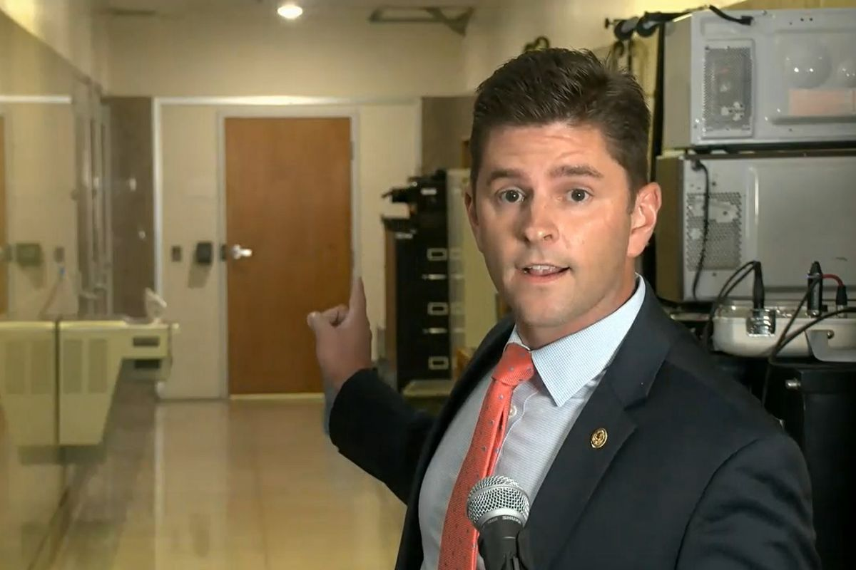 State Rep. Ryan Spain, R-Peoria, points to the door to the room where Democrats are drawing new legislative maps in Springfield earlier this month.