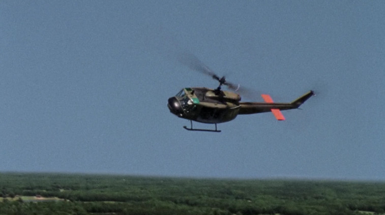 A black helicopter is flying over a green grassy field.