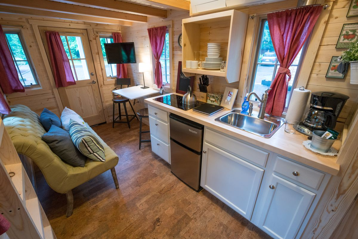A kitchen, dining room, and small couch in a tiny home.