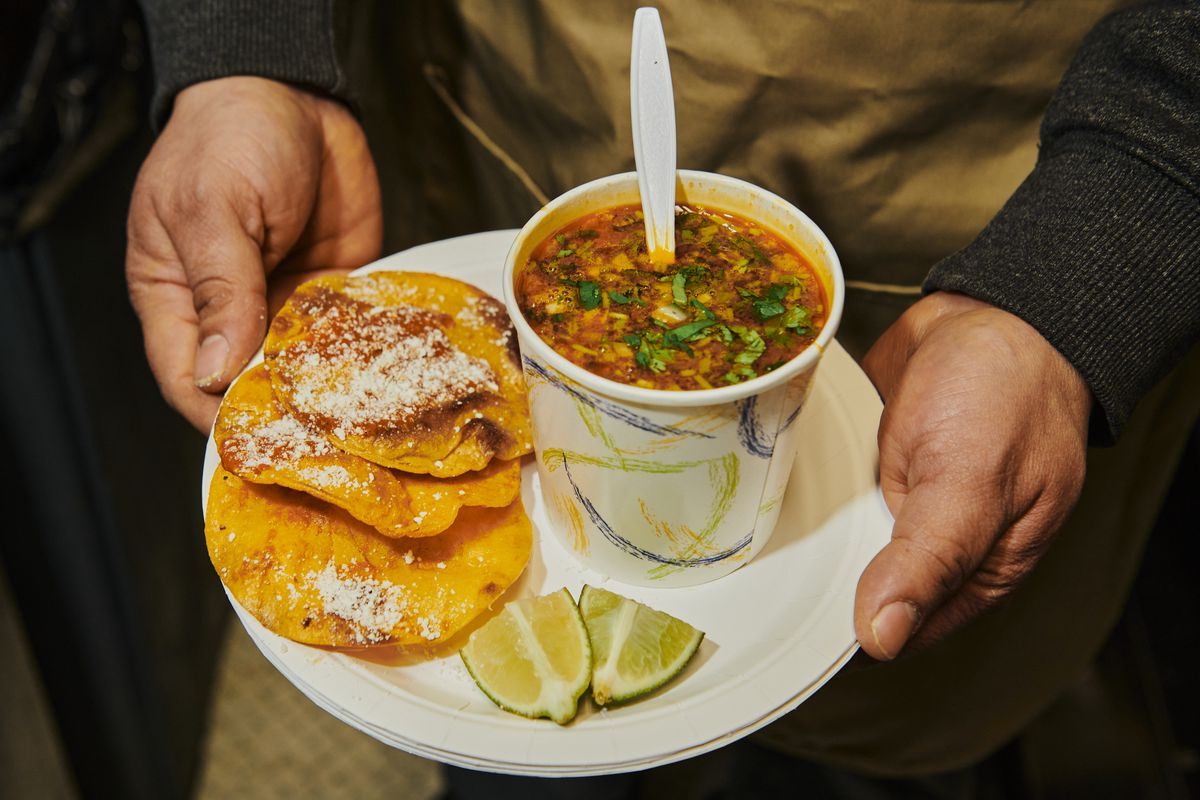 Two hands hold a disposable plate with three tostadas, a cup of brothy consomé, and two lime wedges