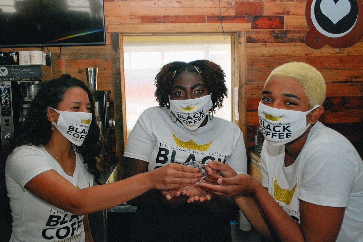 Three young baristas wearing face masks hold up a glass at Black Coffee Northwest in Shoreline.