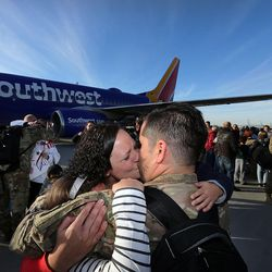 Carla Vargas kisses her husband, Sgt. Abel Vargas, as soldiers from Detachment 2, 101st Airborne Division (Air Assault) return to Utah on Friday, Nov. 18, 2016, following an 11-month deployment to Iraq. They are holding their children Oliver and Karina.