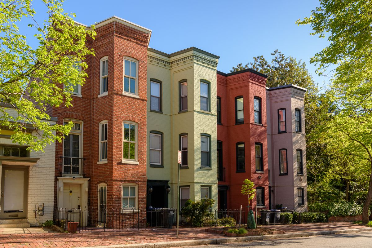 A row of colorful brick townhouses on a residential street. The homes are three stories tall.