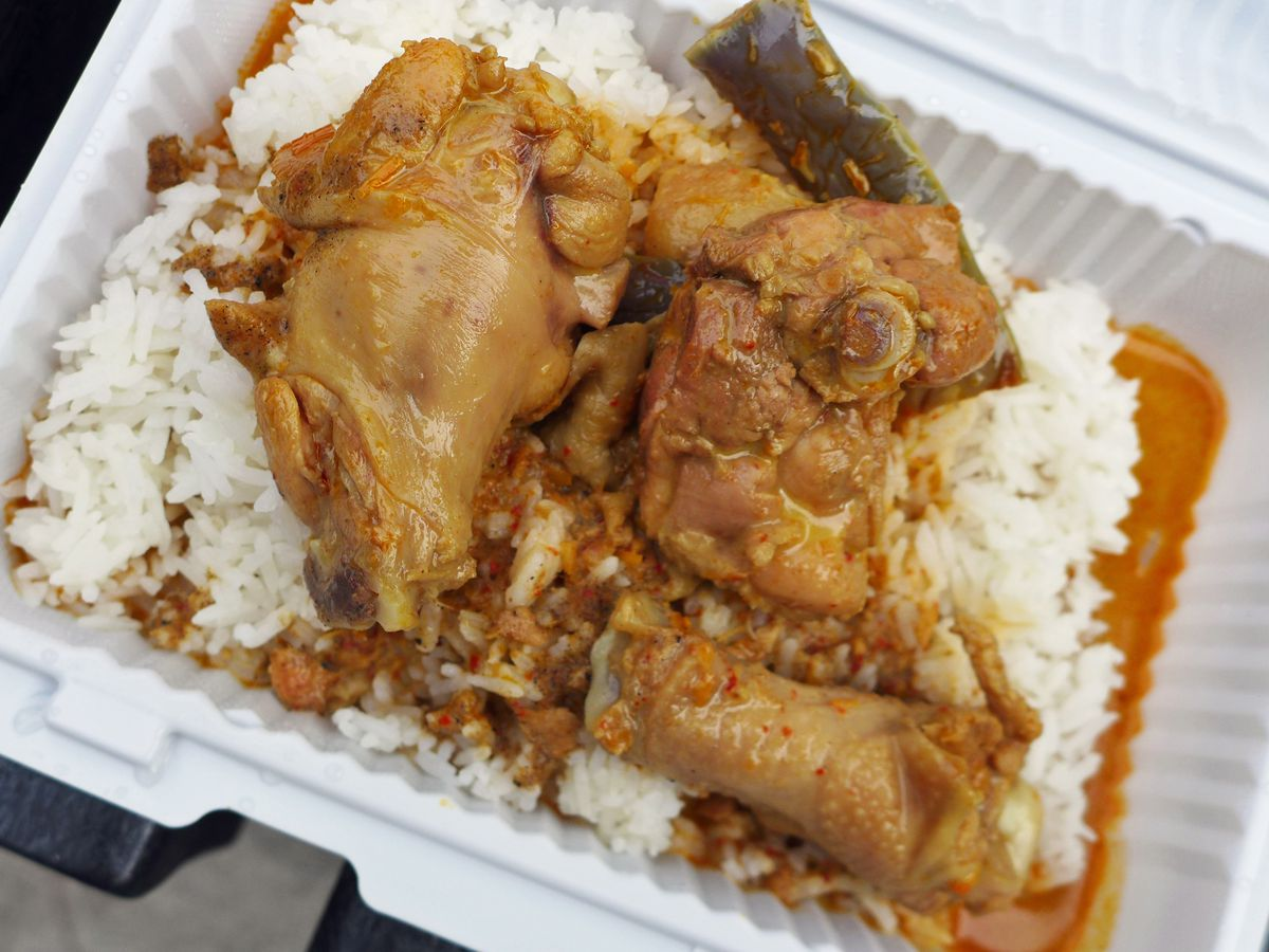 A chicken in a yellowish red sauce on a bed of white rice.