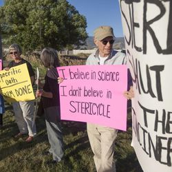 Allan Posner, right, holds a sign during a rally asking Utah Gov. Gary Herbert to shut down Stericycle's medical waste incinerator in North Salt Lake on Thursday, Sept. 25, 2014.