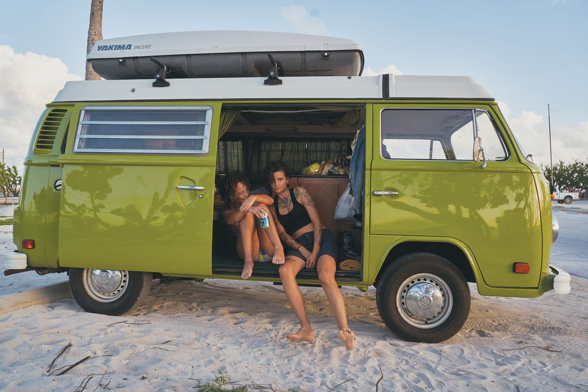 A couple sits inside a green Volkswagen.