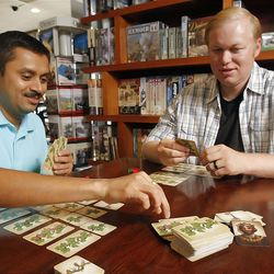 Game designers, Sandeep Kharkar, left, and Dave Haslam demonstrate their game King's Vineyard Tuesday, July 19, 2011 at the Game Stop store.