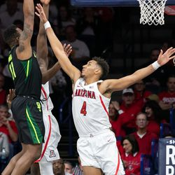 Baylor's Mark Vital (11) goes for a stretch dunk over Arizona's Chase Jeter (4) in the first half of the Arizona-Baylor game in McKale Center on December 15 in Tucson, Ariz.