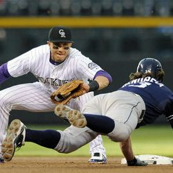 Colorado Rockies shortstop Troy Tulowitzki tags out San Diego Padres Chris Denorfia on an attempted steal of second base during the second inning of a baseball game Tuesday, April 17, 2012, in Denver.