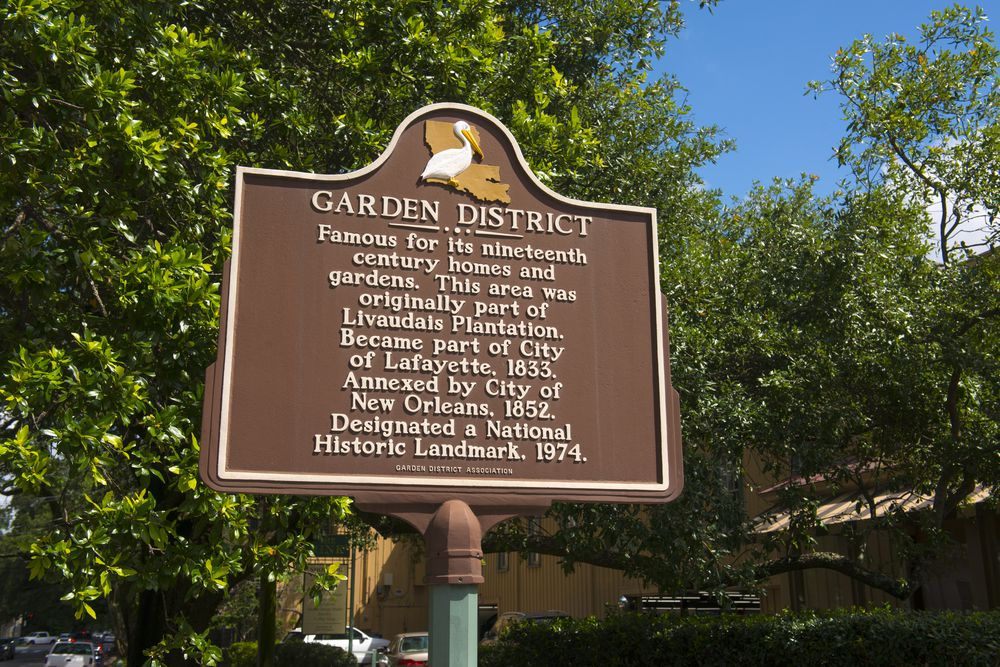 A brown sign with words that read: Garden District.
