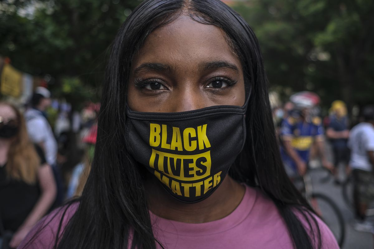 A woman wearing protective mask with Black Lives Matter...